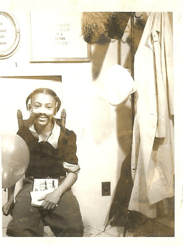 A Black girl sits on a high-backed chair, smiling at the camera.  She has two pigtails, is wearing a mustache, and holds a balloon and some pictures.  To the right is a coat rack with items hanging from it.