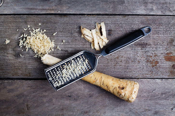 Grated horseradish root with grater on w