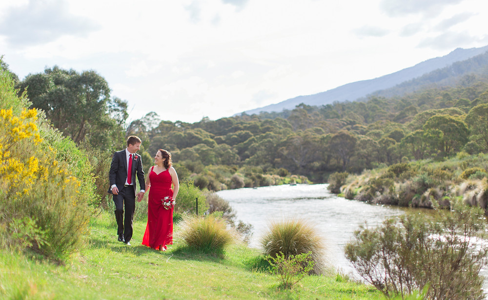 Paul and Reine walk along beside the Thredbo river. Holding hands and gazing into each others eyes on a sunny summer day. Reine's dress is a bright red and Pauls tie matches, while Reine's bouquet of white and red origami roses is held beside her hip.