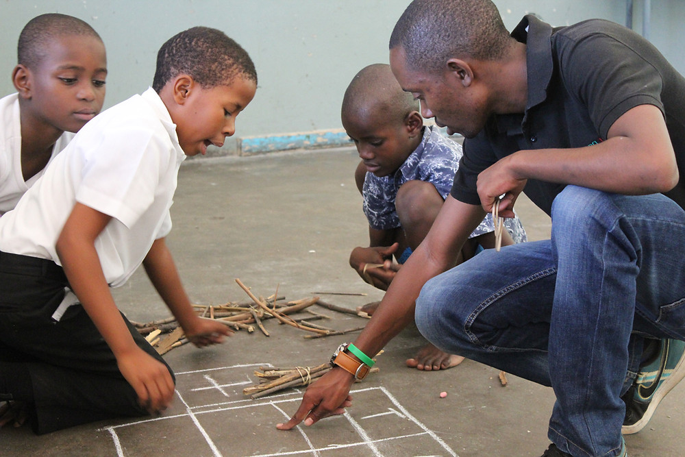 A Young 1ove TaRL facilitator explains a maths sum to learners