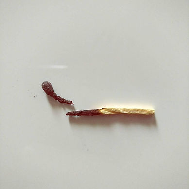 Matchstick Singles album cover, a burnt and broken match on a white background under stark lighting