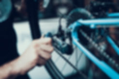 Mechanics Hand Repairing Bicycle in Bike