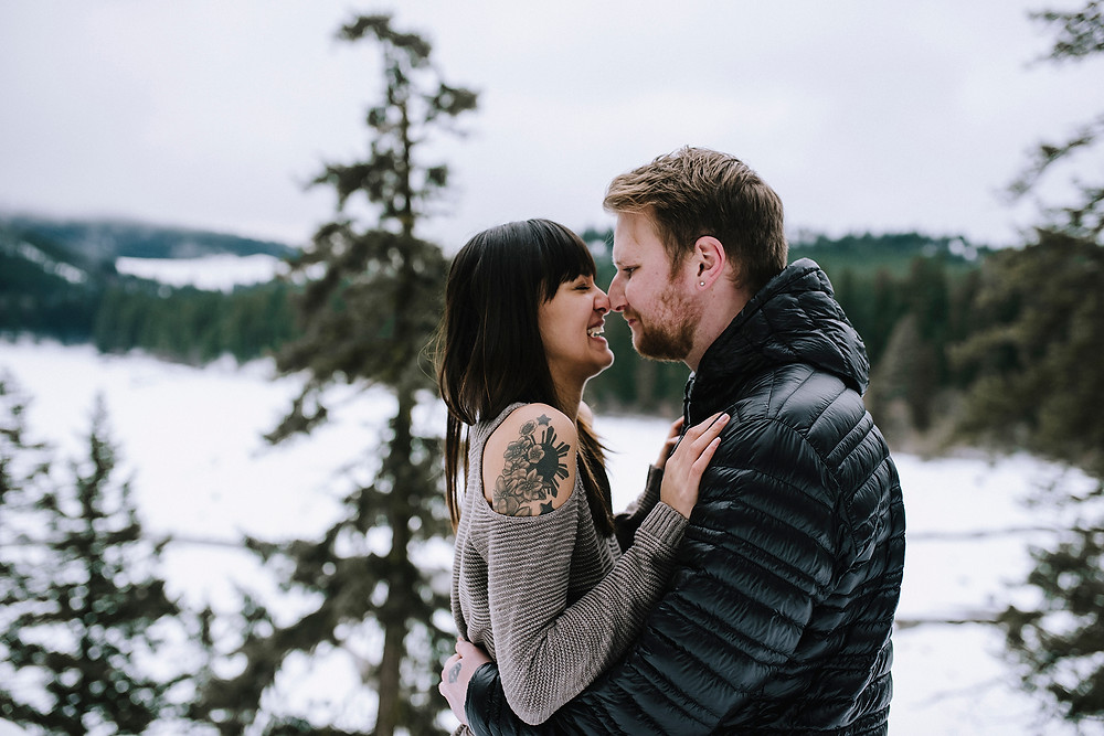 Makenna & Lucas' Engagement touching noses in the snowy forest
