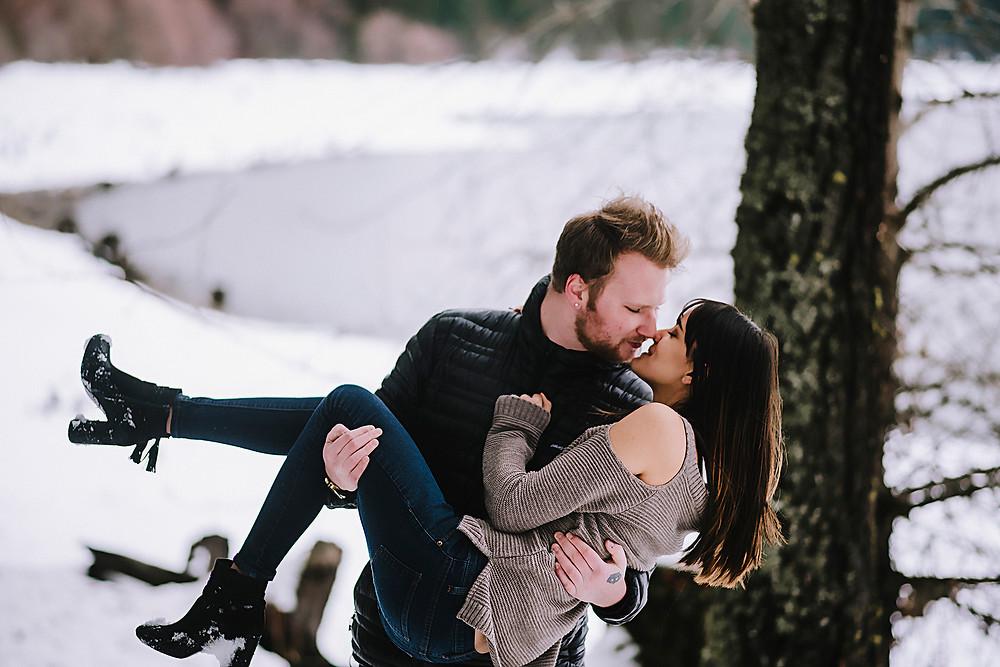 Couple about to kiss near a frozen lake