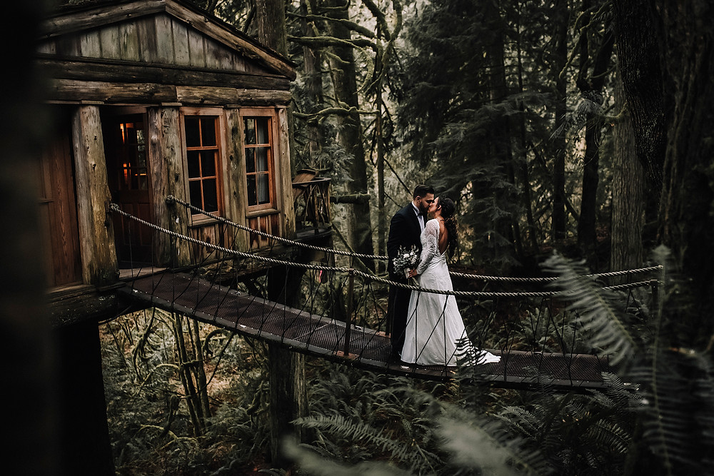 Treehouse Wedding bride and groom kissing on the suspension bridge
