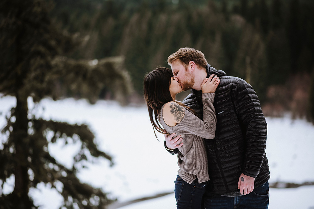 Engagement photos, couple kissing in snowy forest