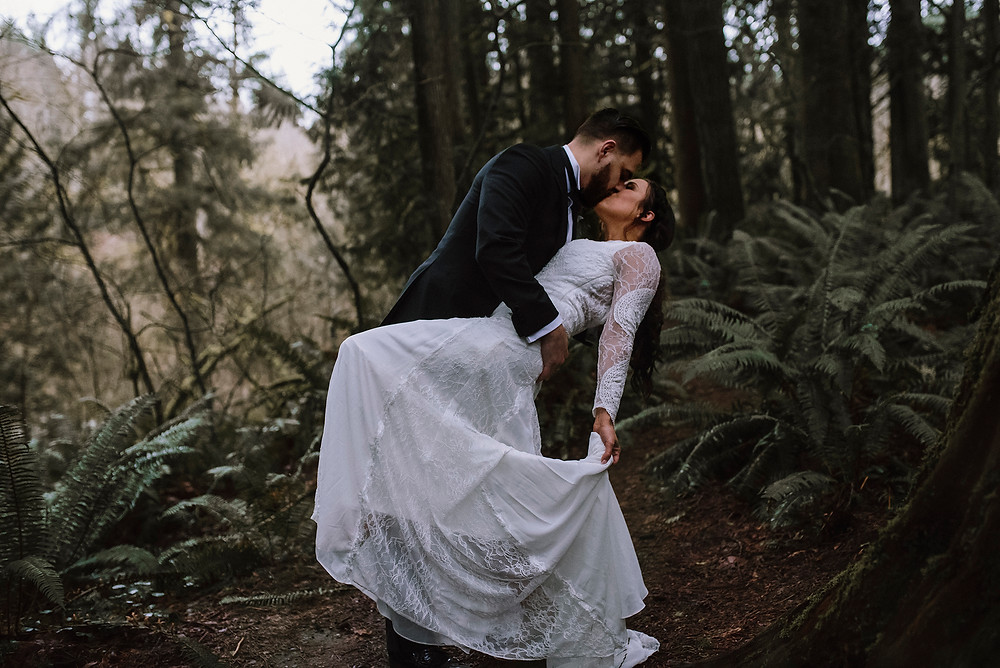 Bride and groom kissing in the forest, sword ferns and evergreen trees