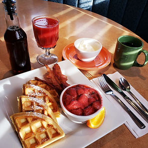 Belgian Waffles with strawberry compote, whipping cream, bacon, coffee, maple syrup and tomato juice.