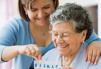 Dame âgée qui joue au carte avec sa famille d'accueil pour personne âgée