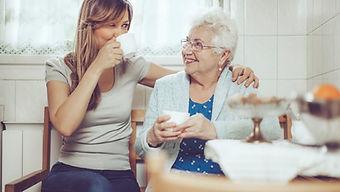 Famille d'accueil pour personnes âgées qui prend un café avec son accueillie
