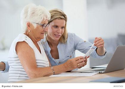 Une personne âgée se fait aider par sa Famille d'Accueil pour replir ses papiers administratifs