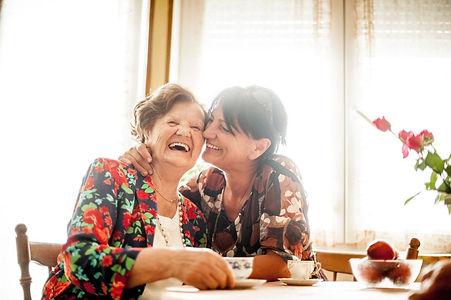 Dame âgée qui rie avec sa famille d'accueil