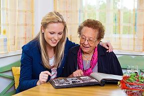 Famille d'accueil pour personnes âgées qui regarde des photos avec son accueillie