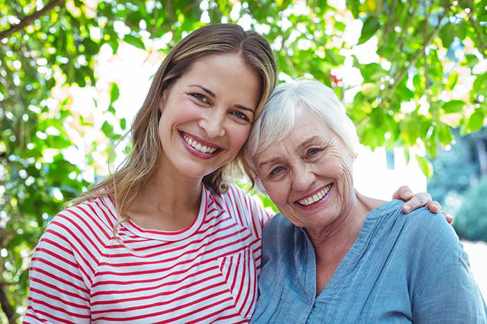 Accueillante familial qui sourit avec la personne âgée vivant chez elle