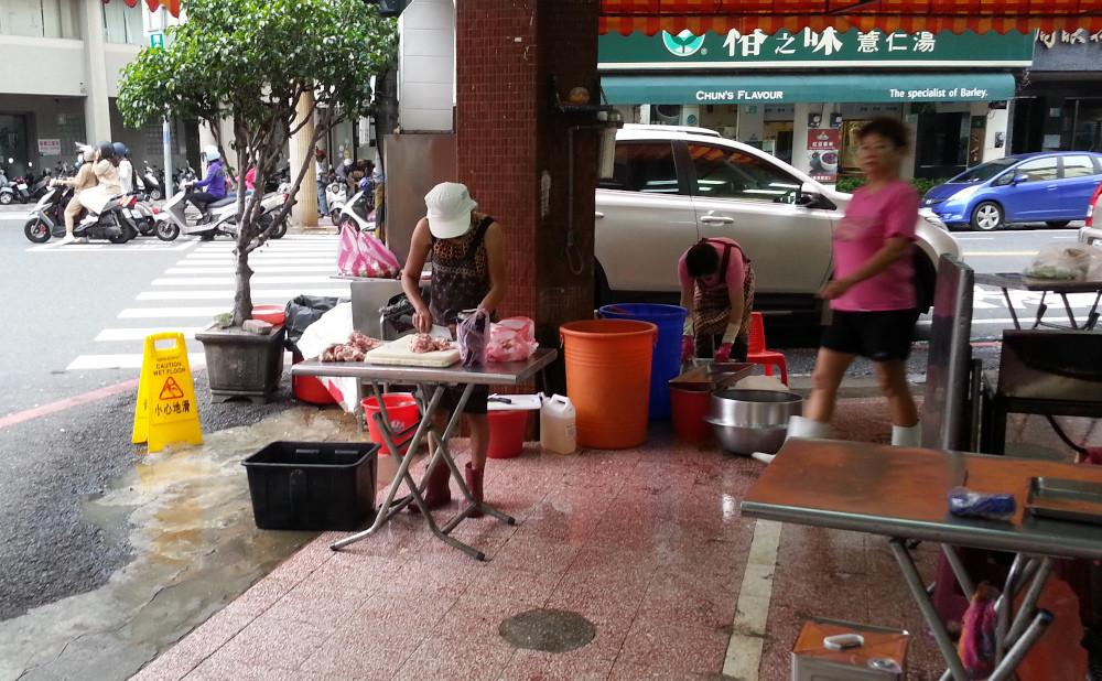 Women preparing food on the sidewalk