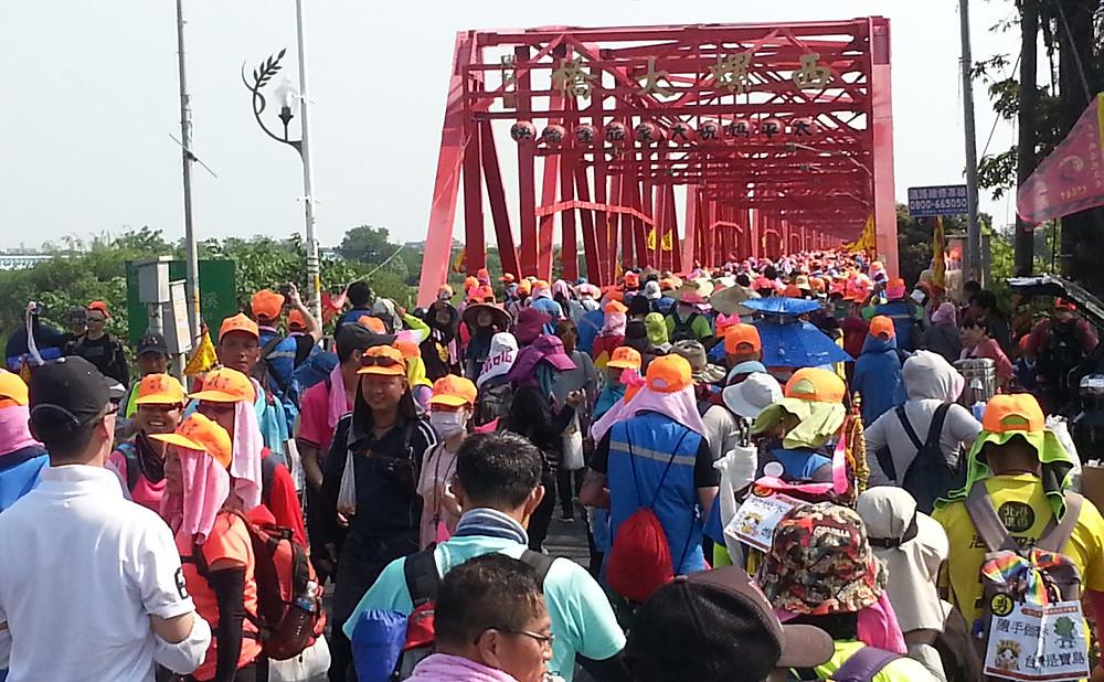 Crowd of pilgrims walking on the Siluo bridge