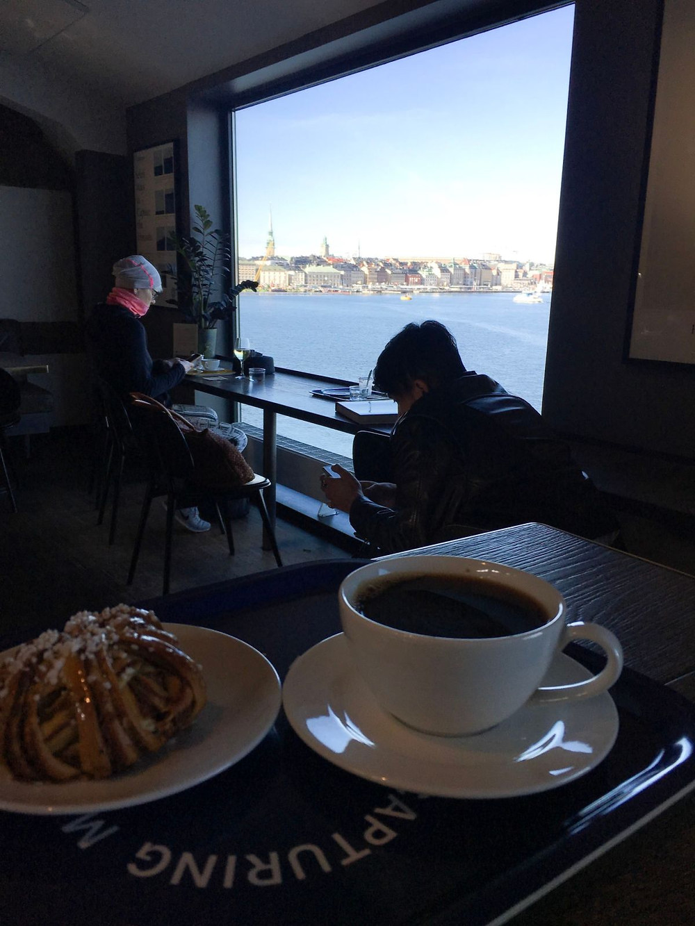 Cup of coffee and cinnamon pastry on a table overlooking the Stockholm archipelago