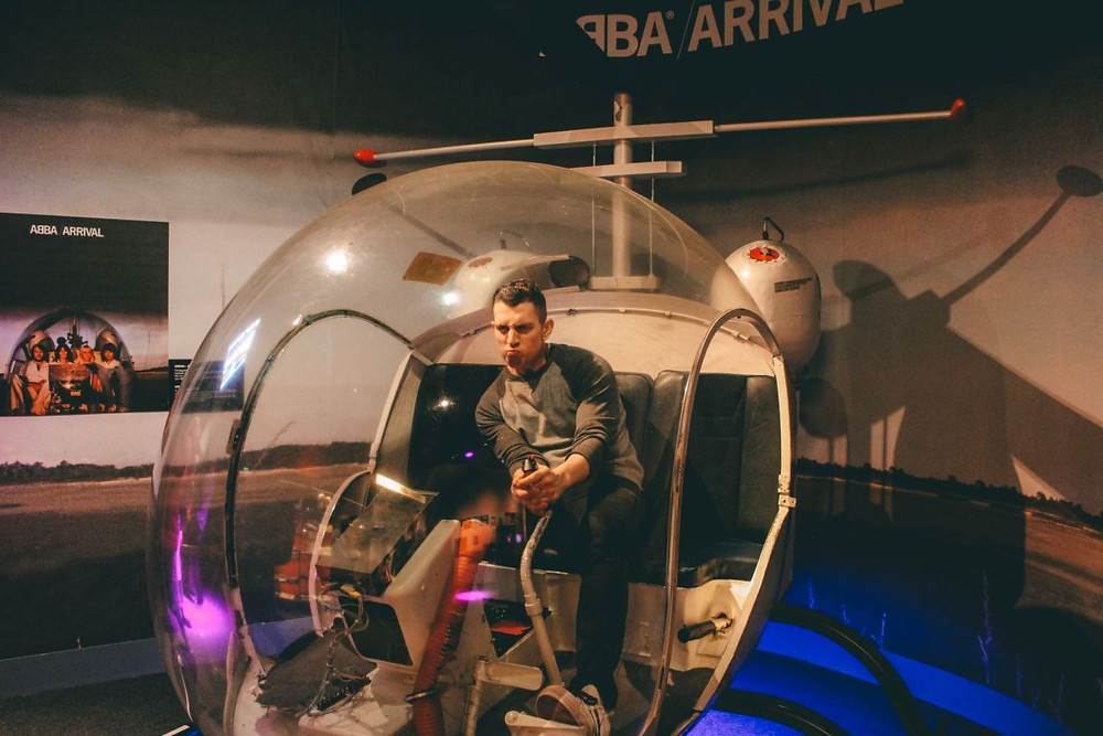 Man driving a glass round helicopter inside the ABBA Museum