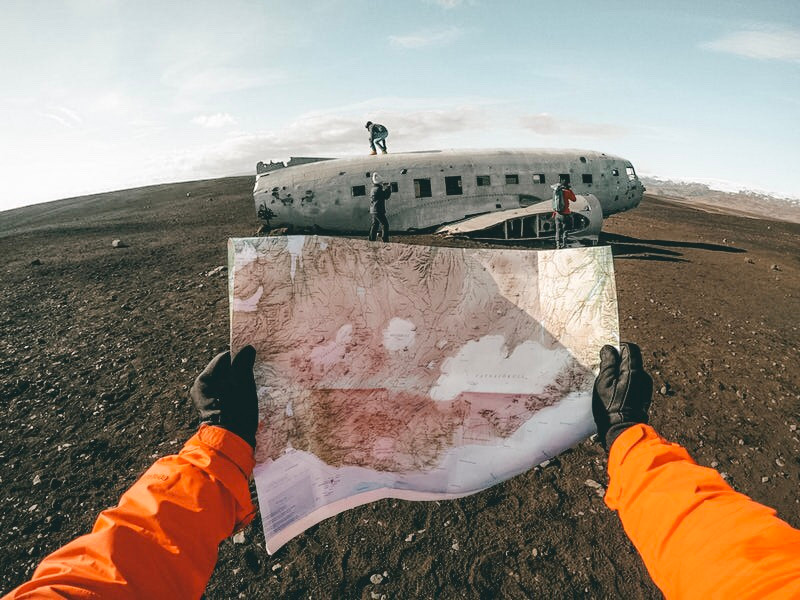 Person holding a map in front of the Sólheimasandur plane crash site in Iceland