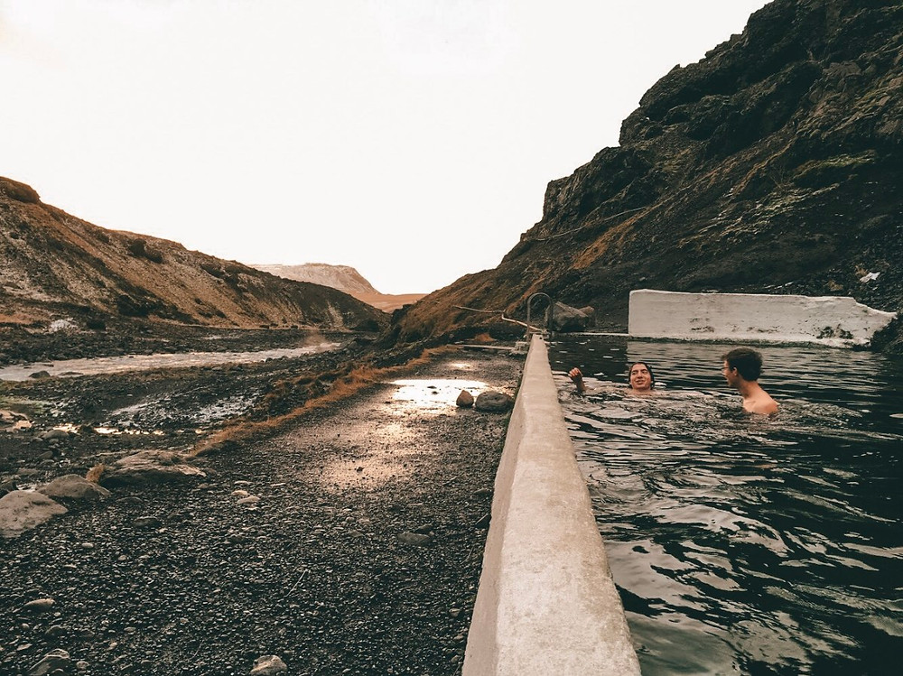 Two men swimming in a pool built into the mountainside
