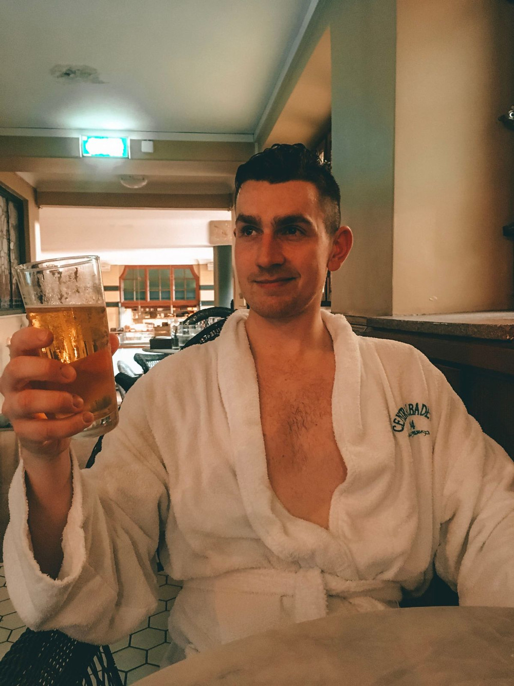 Man in white robe holding up a glass of beer in a European spa