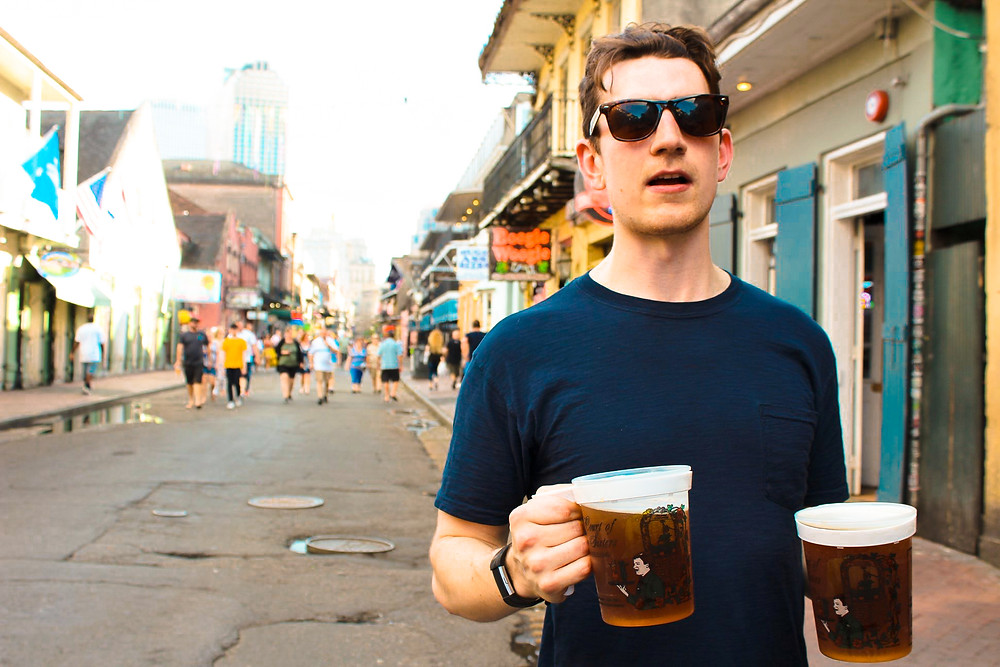 Man in blue shirt holding two plastic mugs of beer on Bourbon Street