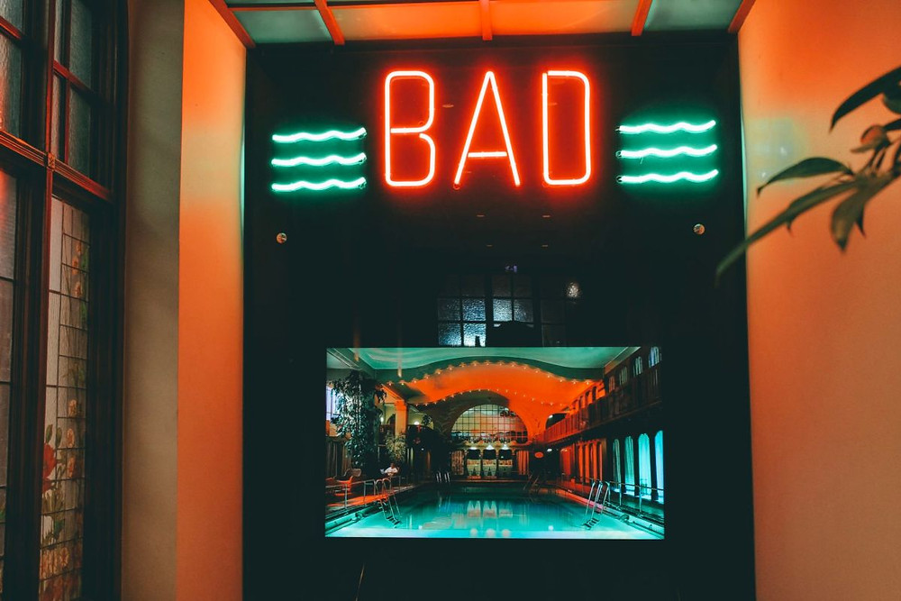 "Sign saying ""Bad"" marking the entrance to Centralbadet with a picture of a pool within the spa"