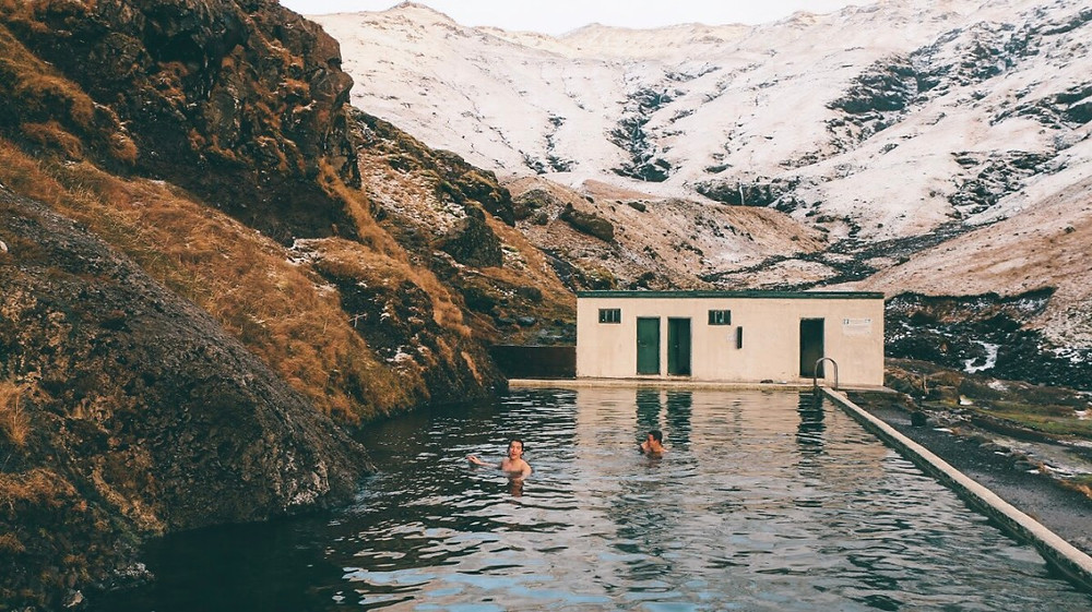 Two men swimming in Seljavallalaug pool with changing room building behind