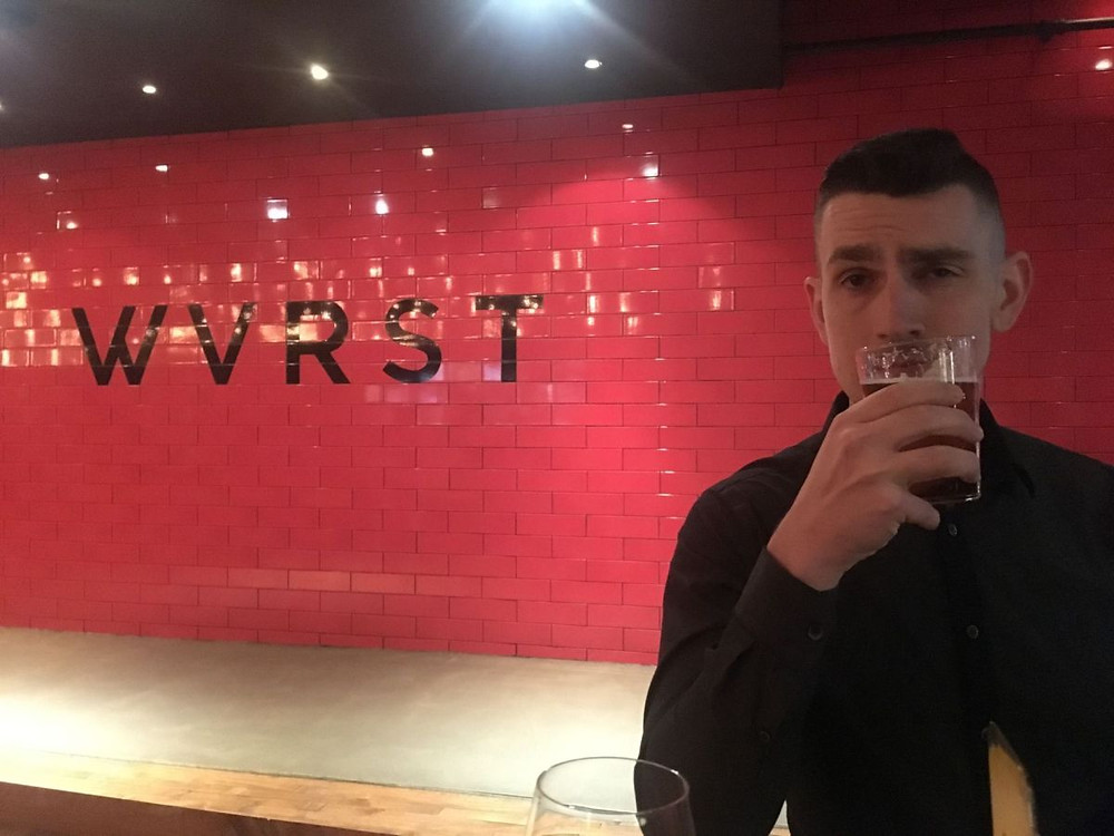"Red subway tile wall with ""Wvrst"" written on it and man drinking a beer"
