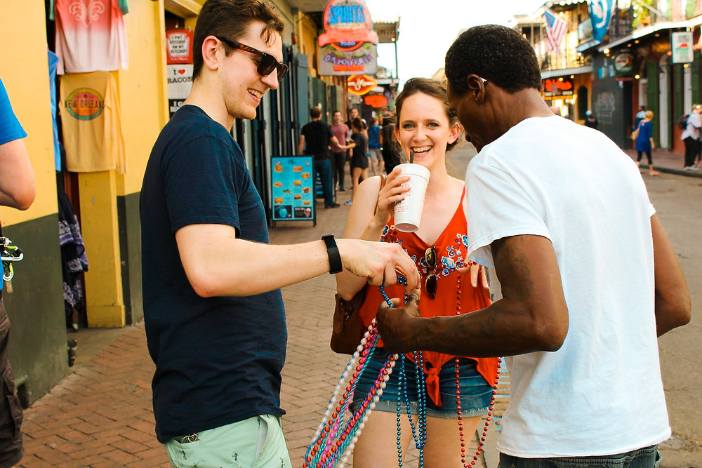 Man trying to sell Mardi Gras beads to a man and woman drinking frozen daiquiris on Bourbon Street