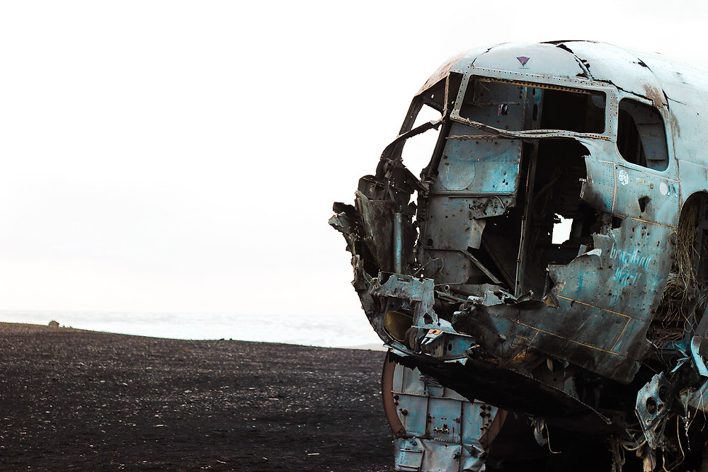 plane with torn open front on a black sand beach