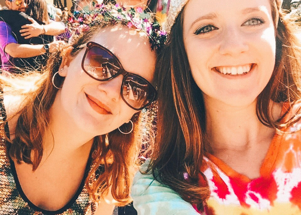 Two girls smiling at camera wearing rainbow clothes and shiny accessories for Mardi Gras