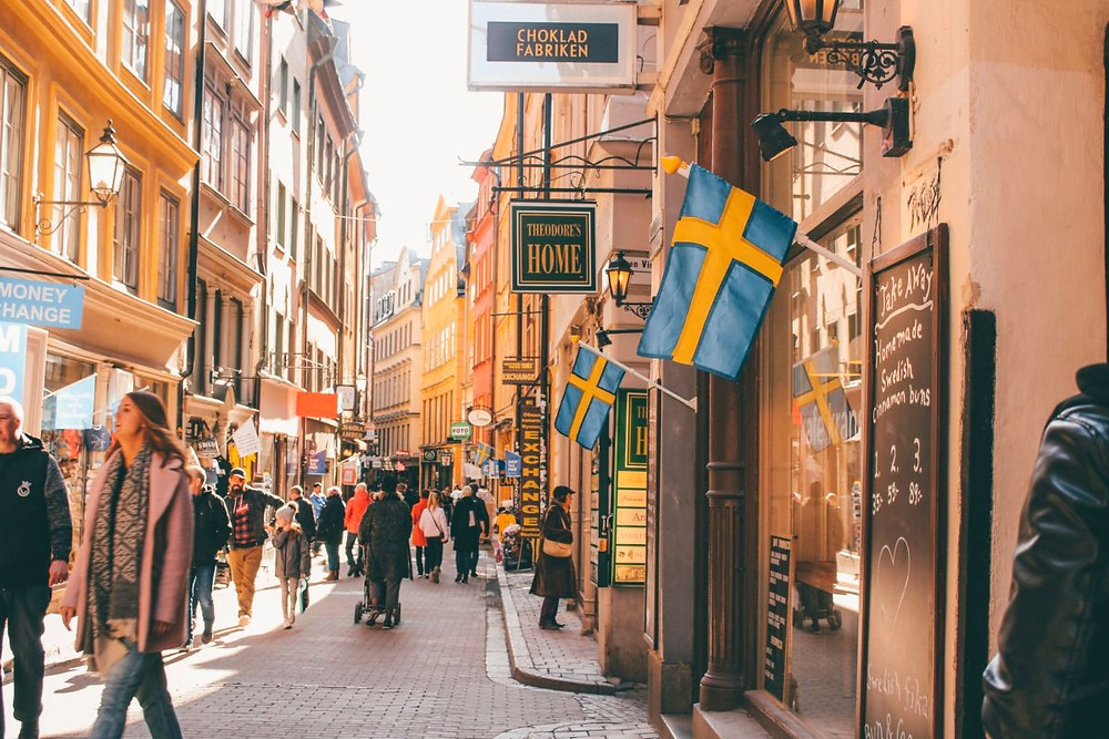 View of a street lined with souvenir shops and Swedish flags