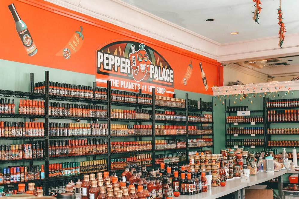 """A red and green wall of hot sauces and salsas under a sign that says """"Pepper Palace"""""""