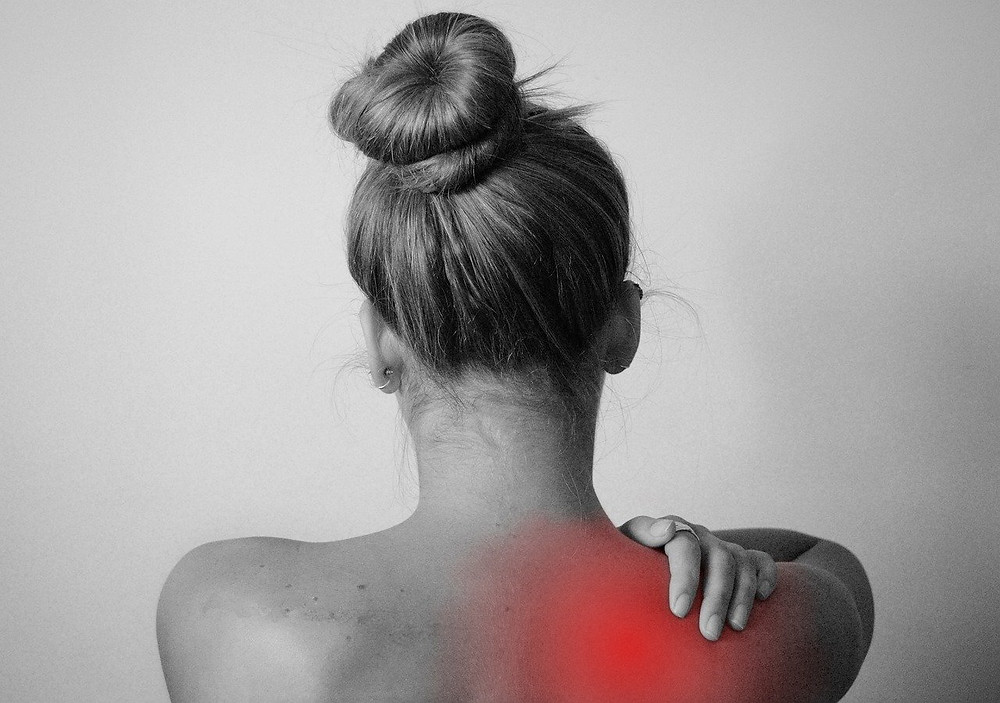 back view of woman holding her painful shoulder myofascial release targets pain