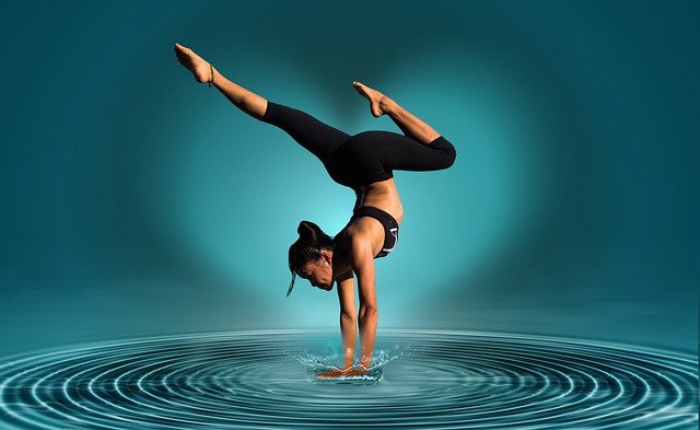 Female gymnast doing a handstand in water