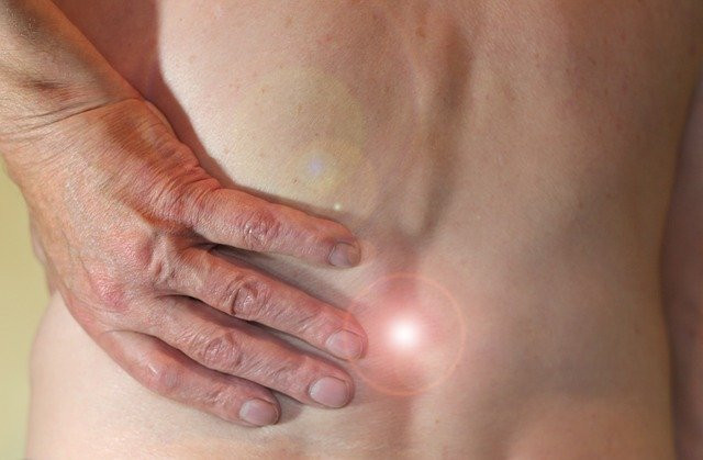 view of man's bare back with his hand holding a painful spot