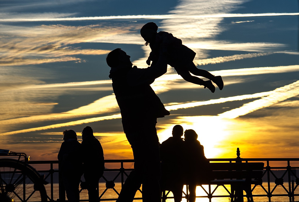 silhouette of father swinging child in the air against a sunset background with full mobility and pain free