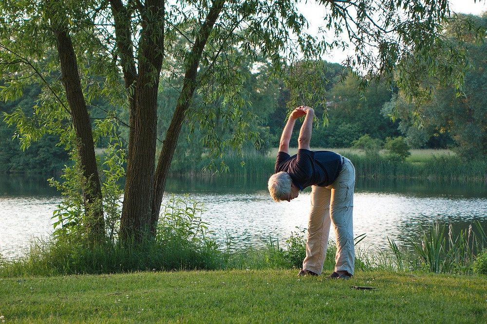 elderly man on a river bank bending forwards with hands clasped behind him showing no sign of mobility issues or pain