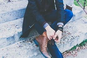Mann in Sakko seine Schuhe binden