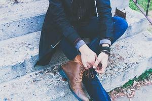 彼の靴を結び付けるスポーツジャケットの男