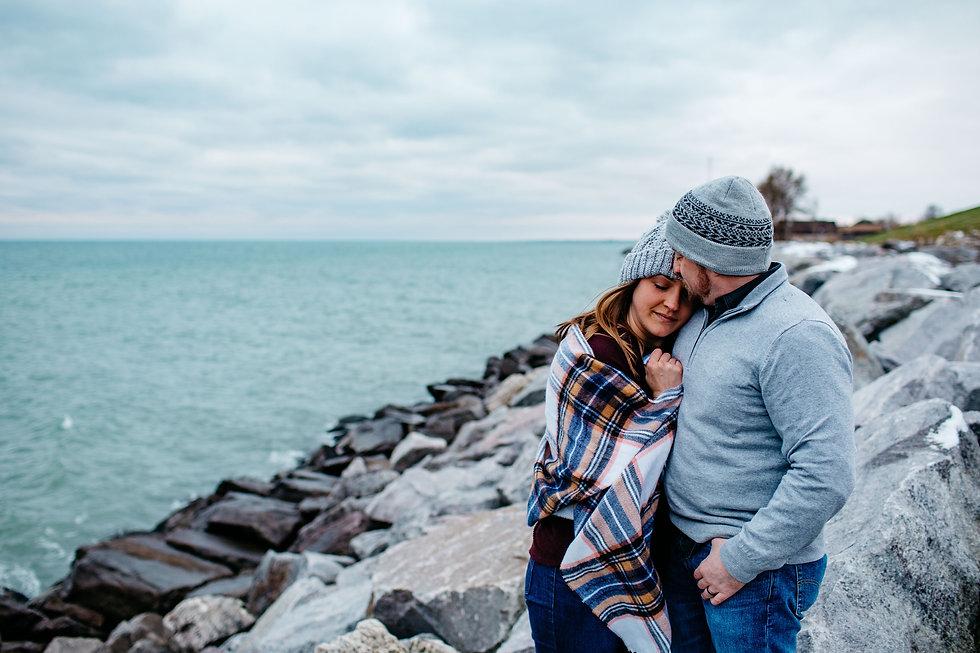 Couple hugging on rocky banks of Lake Michigan