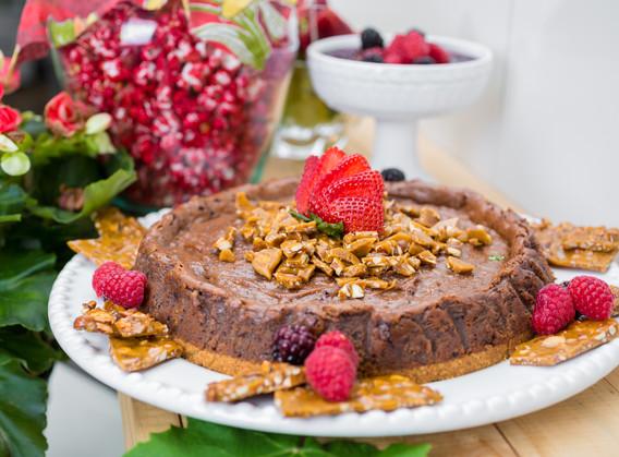 Cheesecake de Ovomaltine com praliné de nuts e calda de chocolate meio amargo.