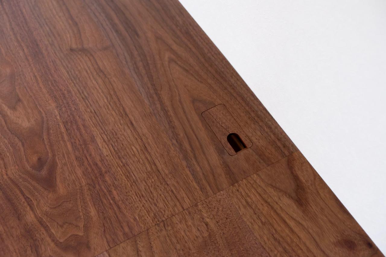 天板に開いた通線孔。同じ無垢材でフタを作っています