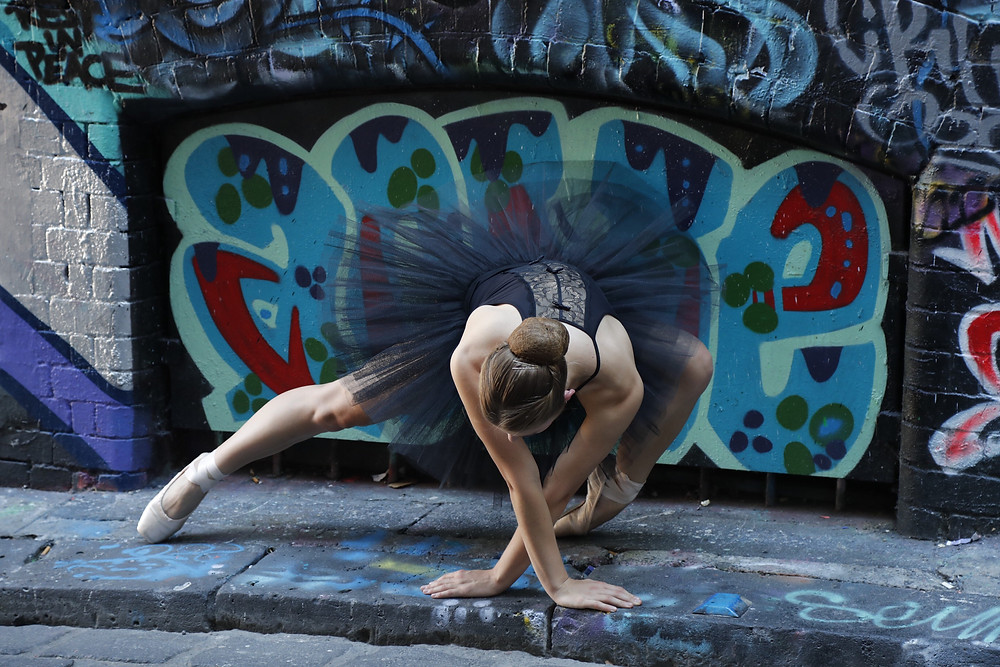 A ballerina poses in front of graffiti at the Flanders Lane end of Hosier Lane, which is renowned for its end to end wall art!