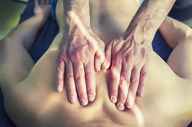deux mains jointes massant le haut du dos