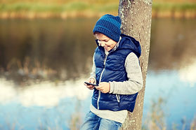 happy-boy-playing-game-on-smartphone-out