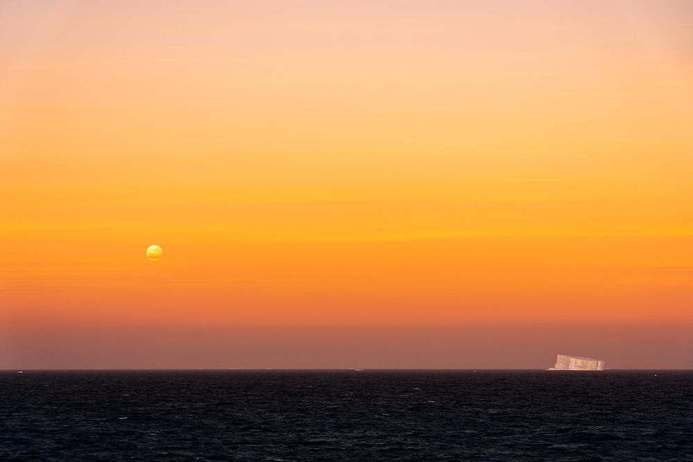 moon sets at sunrise with iceberg