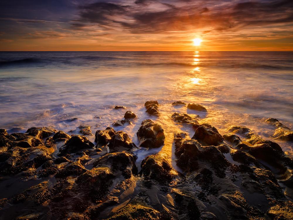 sunset over waves crashing on rocks