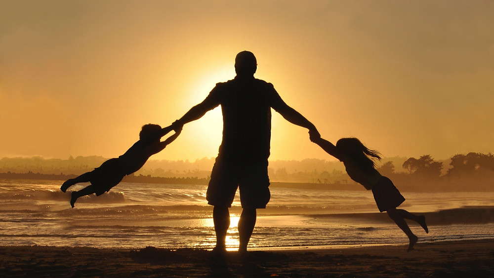man with kids at sunset on beach